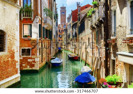 The Rio di San Cassiano Canal with boats and colorful facades of old medieval houses in Venice, Italy. Bell-tower of San Cassiano (Church of Saint Cassian) is visible in background. - stock photo