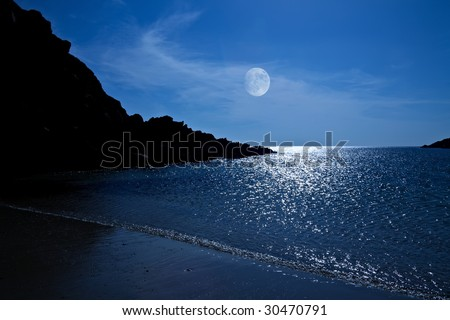 The rising moon reflected in the ocean from a beautiful bay - stock photo