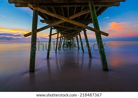 The rising sun paints the sky over the sea with vivid colors as seen from beneath the Bogue Inlet Fishing Pier in Emerald Isle, North Carolina. - stock photo