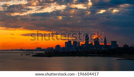 The rising sun touches the corner of a nearly silhouetted office tower in Cleveland Ohio - stock photo