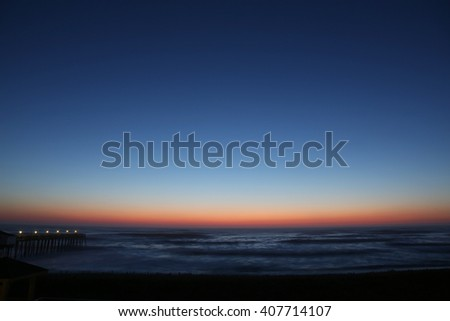 The rising sun visible through pier supports and is reflected in waves by the Nags Head fishing pier on the outer banks of North Carolina - stock photo