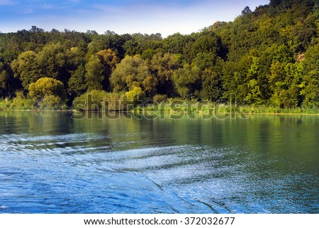 the river the Southern Bug around beautiful coastline of hills with green trees and blue sky - stock photo