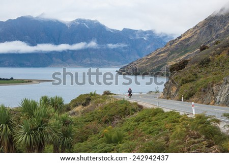 The road beside the lake in a cloudy weather - stock photo