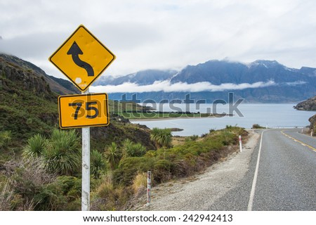 The road beside the lake in a cloudy weather and control limit speed sign board - stock photo