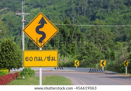 The road curved like a snake with warning sign - stock photo