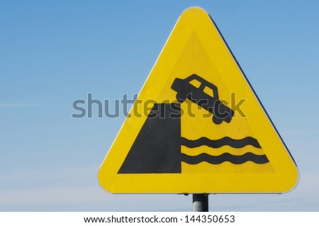 The road ends against water warning sign - stock photo
