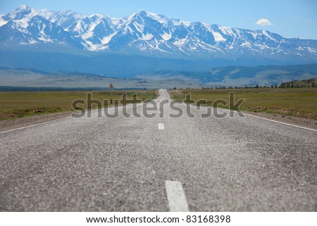 The road in the mountains straight as an arrow on the background of eternal snow - stock photo