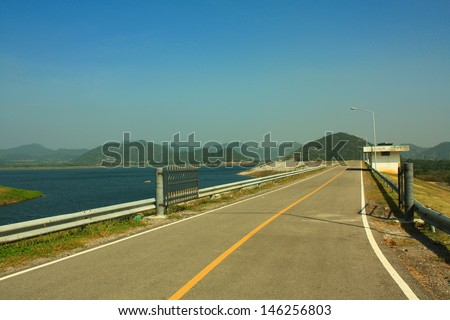 The road on the earth dam. - stock photo