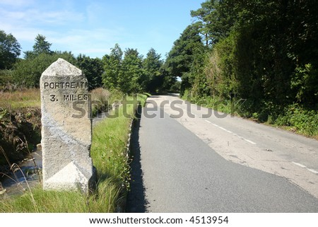 The road to Portreath, Cornwall and an old English milestone. - stock photo