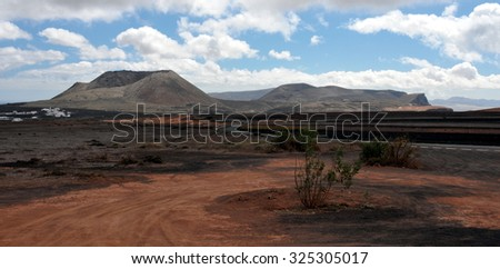 The road to the top of the mountain Mirador del Rio on background blue sky. Gravel slopes of the volcano on the island of Lanzarote. Canary Islands, Spain - stock photo