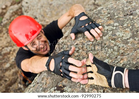 The rock climber gives hand for help to the partner - stock photo