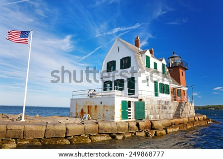 The Rockland Breakwater Lighthouse on a summer afternoon, with US flag flying. Rockland, Maine, USA - stock photo
