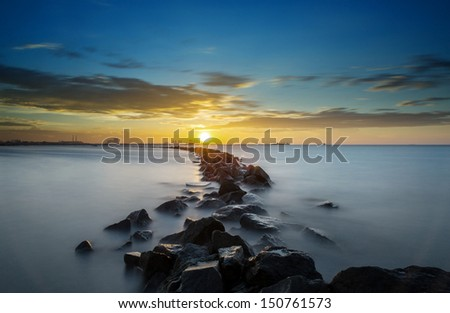 the rocks, beach and the sunset - long exposure - stock photo