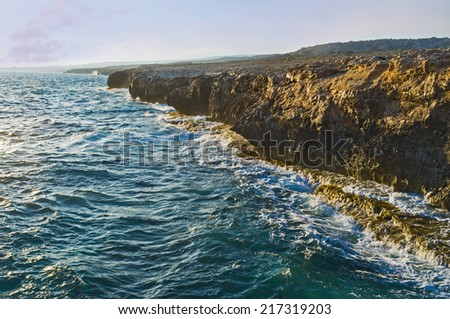 The rocky coastline of the Cape Greco and the stormy sea colored in the evening rays of sun, Cyprus. - stock photo