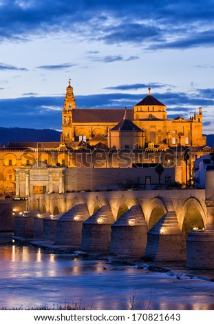 The Roman Bridge (Puente Romano) over Guadalquivir river and Mosque Cathedral (Mezquita) at twilight in Cordoba, Andalusia, Spain. - stock photo