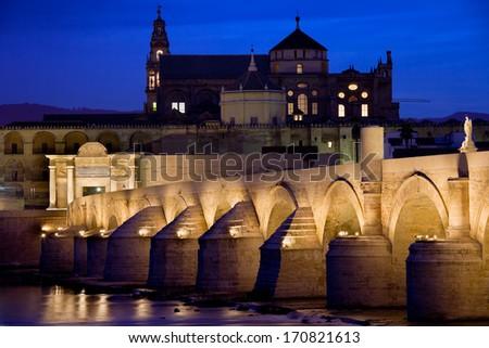 The Roman Bridge (Puente Romano) over Guadalquivir river and Mosque Cathedral (Mezquita) at dawn in Cordoba, Andalucia, Spain. - stock photo