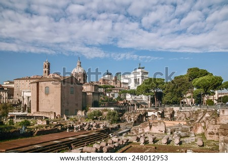 The Roman Forum is a rectangular forum (plaza) surrounded by the ruins of several important ancient government buildings at the center of the city of Rome. Curia and Santi Luca e Martina church - stock photo
