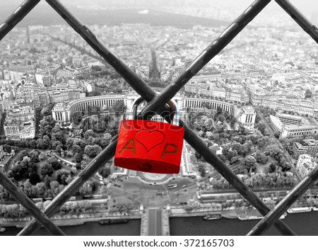 The romantically love inscribed padlocks on the Eiffel Tower, Paris France. In the background panorama of Paris. Black and white wit red element.  - stock photo