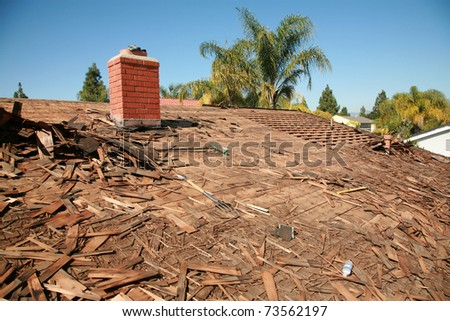 the roof of a house being torn off and being prepaired to be re-roofed with new shingles - stock photo