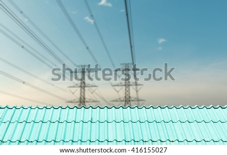 The roof of the house in the background of high-voltage pylons. - stock photo