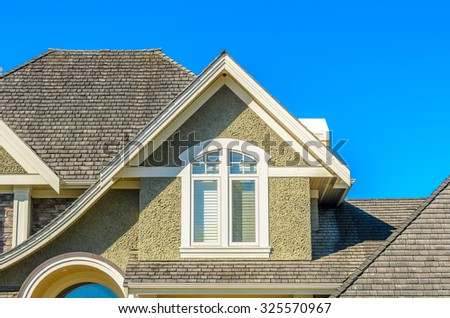 The roof of the house with nice window. - stock photo
