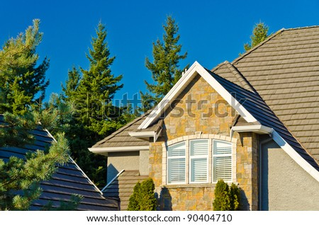the roof of the house with nice window under the blue sky - stock photo