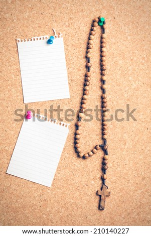 the rosary beads on cork board - stock photo