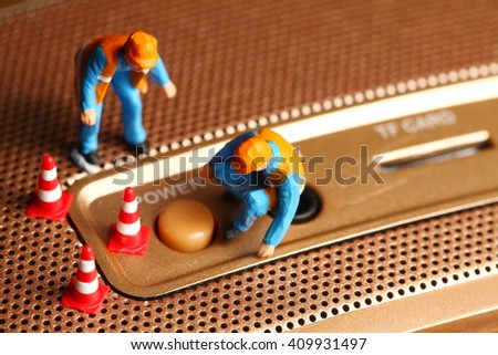 The round power button of the loudspeaker with maintenance miniature figure plastic model represent the speaker sound device and service concept related idea. - stock photo