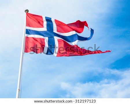 The Royal flag of Norway on a pole towards blue and white sky in daylight - stock photo