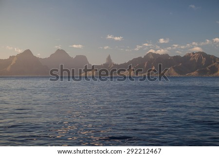 The rugged coastline of the island of Moorea, in French Polynesia, appears on the horizon of the Pacific Ocean. - stock photo