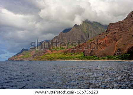 The rugged Na'Pali Coast of Kauai, topped with clouds. - stock photo