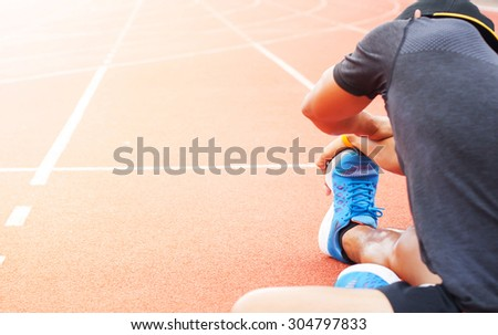the runner athletes stretching on racing track - stock photo