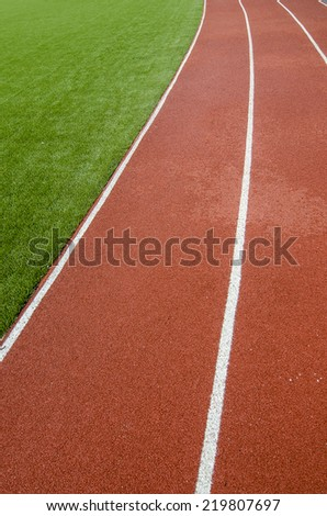The running track rubber lanes in the artificial grass stadium. - stock photo