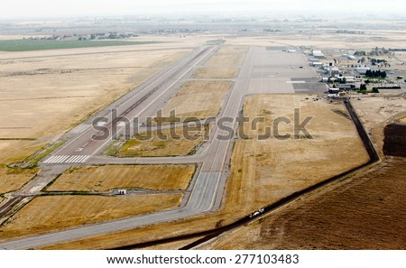 The runway, taxiway, terminal, and aircraft parking at a small city airport. - stock photo
