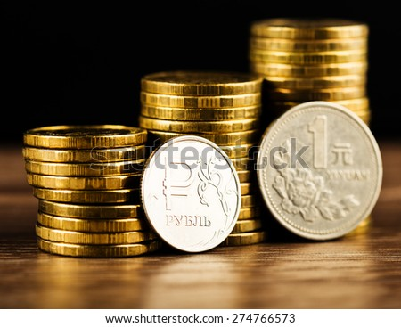The Russian rouble coin and Chinese One Yuan Coin and gold money on the desk - stock photo