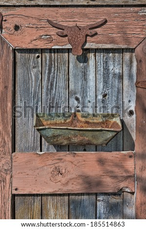 The rusty silhouette of a western steer head is nailed to the weathered door of a shed with a rusted out metal container nailed below it in an artistic garden art collage. - stock photo