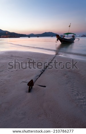 the rybachky boat on an anchor at the coastline on water during sunset - stock photo