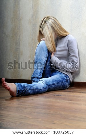 The sad barefooted girl sits on a floor. - stock photo