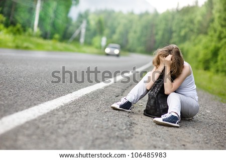 the sad girl hitchhiking along a road. - stock photo
