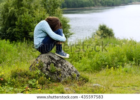 the sad girl in a blue jacket, jeans, gym shoes, with long hair sits on a stone against a grass, trees, water. - stock photo