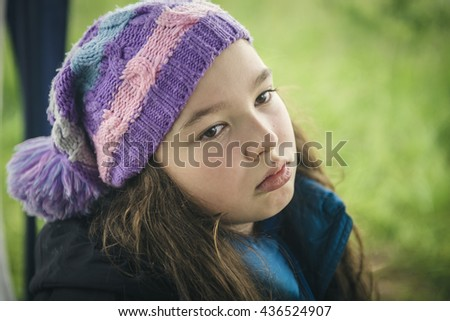 The sad girl in a knitted cap.  - stock photo