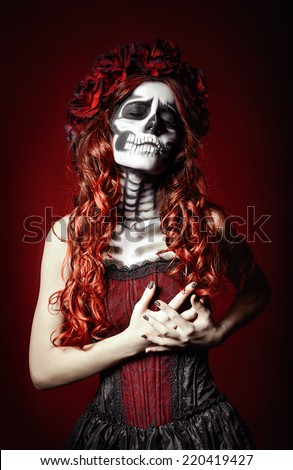 The sad young woman with muertos makeup (sugar skull) holding her chest  - stock photo