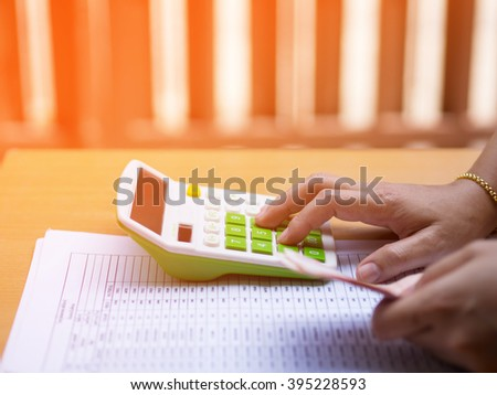 The sales figures  economy  with calculator counting money and making notes  ,  warm tone color . - stock photo