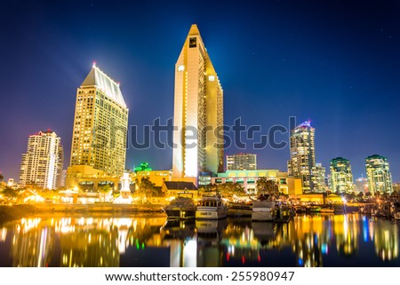 The San Diego skyline and boats at night, seen from Embarcadero Marina Park North, in San Diego, California. - stock photo