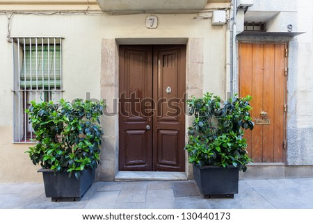 The Sarri� �  quarter of Barcelona was formerly a separate village that, eventually (1921), became part of the city. Here we can see a house's entrance with two big flowerpots on the outside. - stock photo