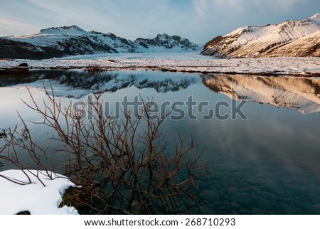 The scenic Vatnajokull National Park in the late afternoon, with snow covered mountains and volcanoes, and calm lakes reflecting the blue skies. - stock photo