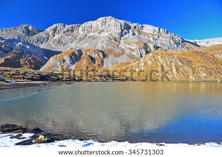 The Schniderhorn reflected in the lake at the Plan des Roses in the Bernese Alps, Switzerland. On a beautiful clear day with snow on the ground - stock photo