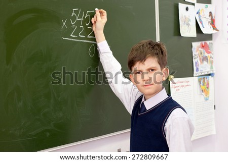 the schoolboy  at the Board decides example - stock photo