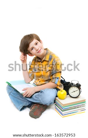 The schoolboy with a pile of books, apple and alarm clocks does homework - stock photo
