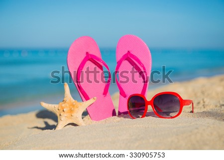 The sea, beach, sand and women's accessories: pink flip-flops, red sunglasses and starfish - stock photo